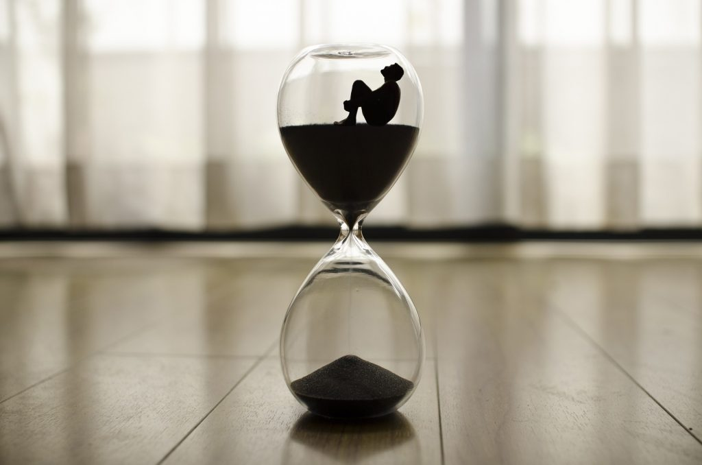 An hour glass is resting on the floor in-front of a closed white curtain. In silhouette there is a man with sitting with his legs to his chest. He is inside the hour glass at the top as the sand flows out from under him into the lower section of the hour glass.