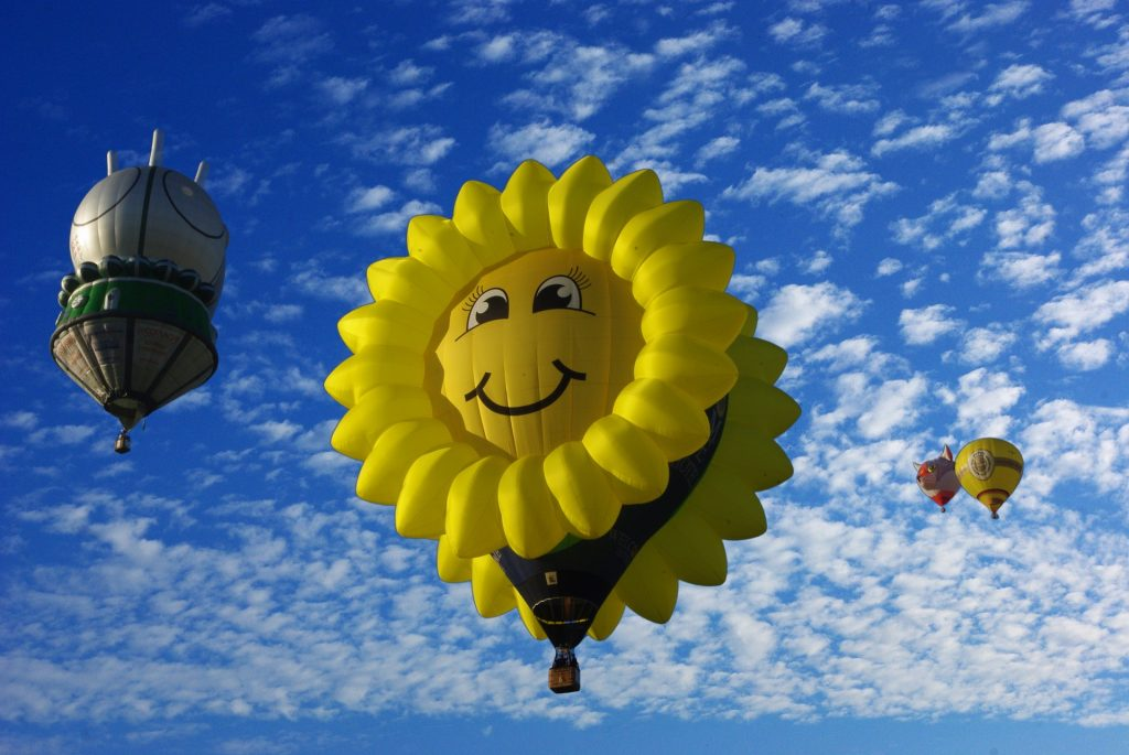 This is a sunflower shaped hot air balloon floating in front of a blue sky dotted with fluffy clouds.