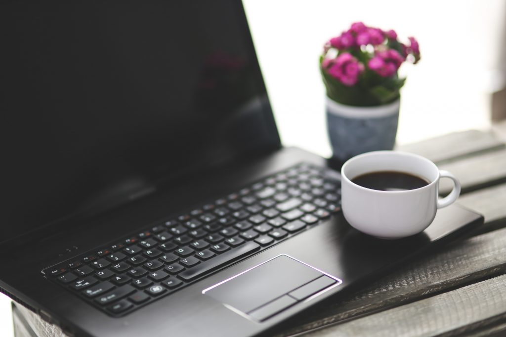 A laptop computer open resting on a window sill. Next to the computer is a small pot of pink flowers. Sitting on the right edge of the laptop computer's key board is a white coffee cup filled with black coffee.