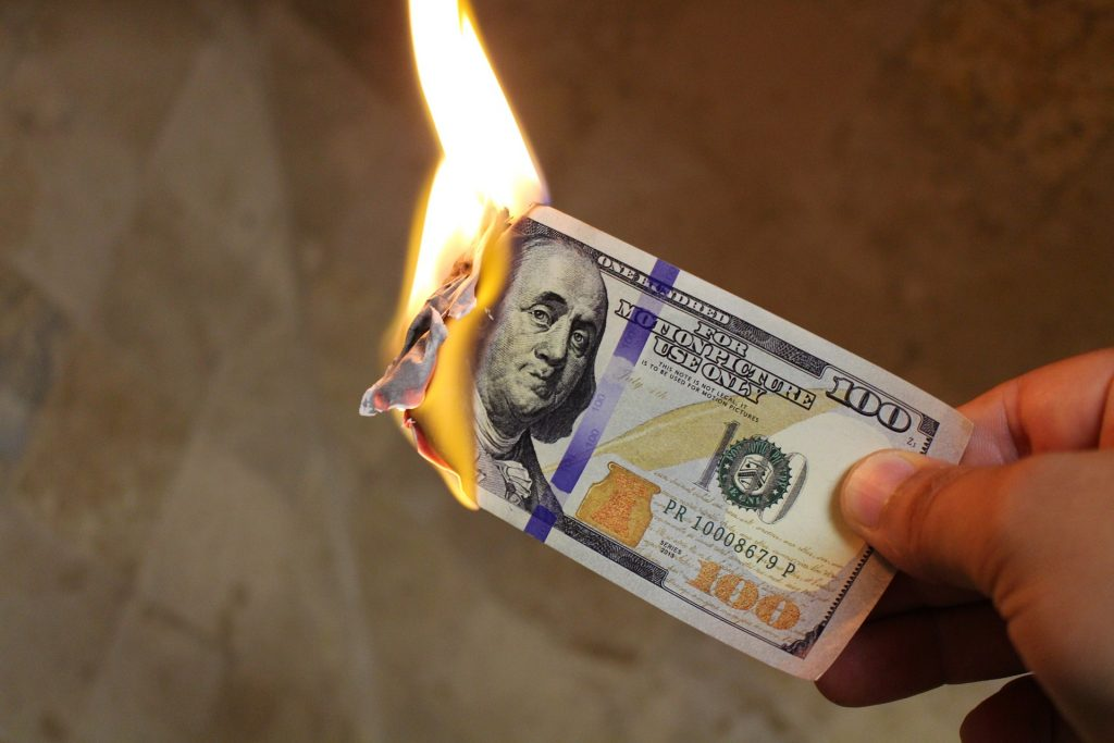 A man's hand is holding a one hundred dollar bill. The has burned to the edge of Ben Franklin's right ear in the portrait. A soft pale yellow flame is rising upward from the burning money.