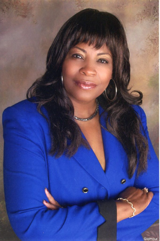 A black woman is posed with her arms crossed low on her chest. She is wearing a blue suit jacket with black lapels